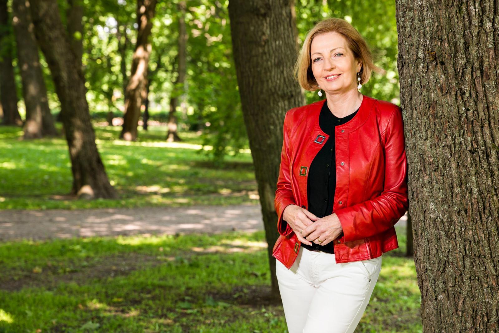 Hyvinvointilomat ry:n puheenjohtaja Anneli Kiljunen nojaa puuhun ja hymyilee aurinkoisessa puistossa.