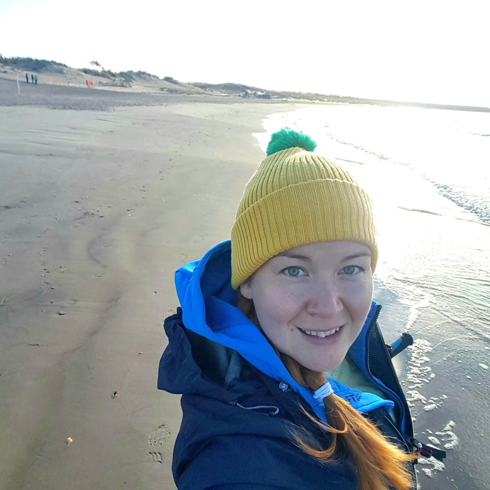 Yyterin kylpylähotellin lomaohjaaja Noora syksyisellä aurinkoisella hiekkarannalla.