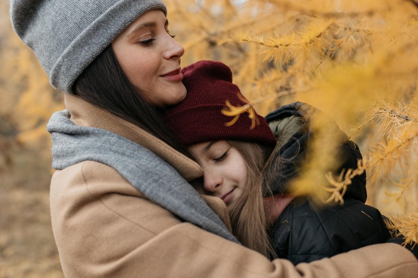 Nainen ja tyttö halaavat toisiaan syksyisessä metsässä.