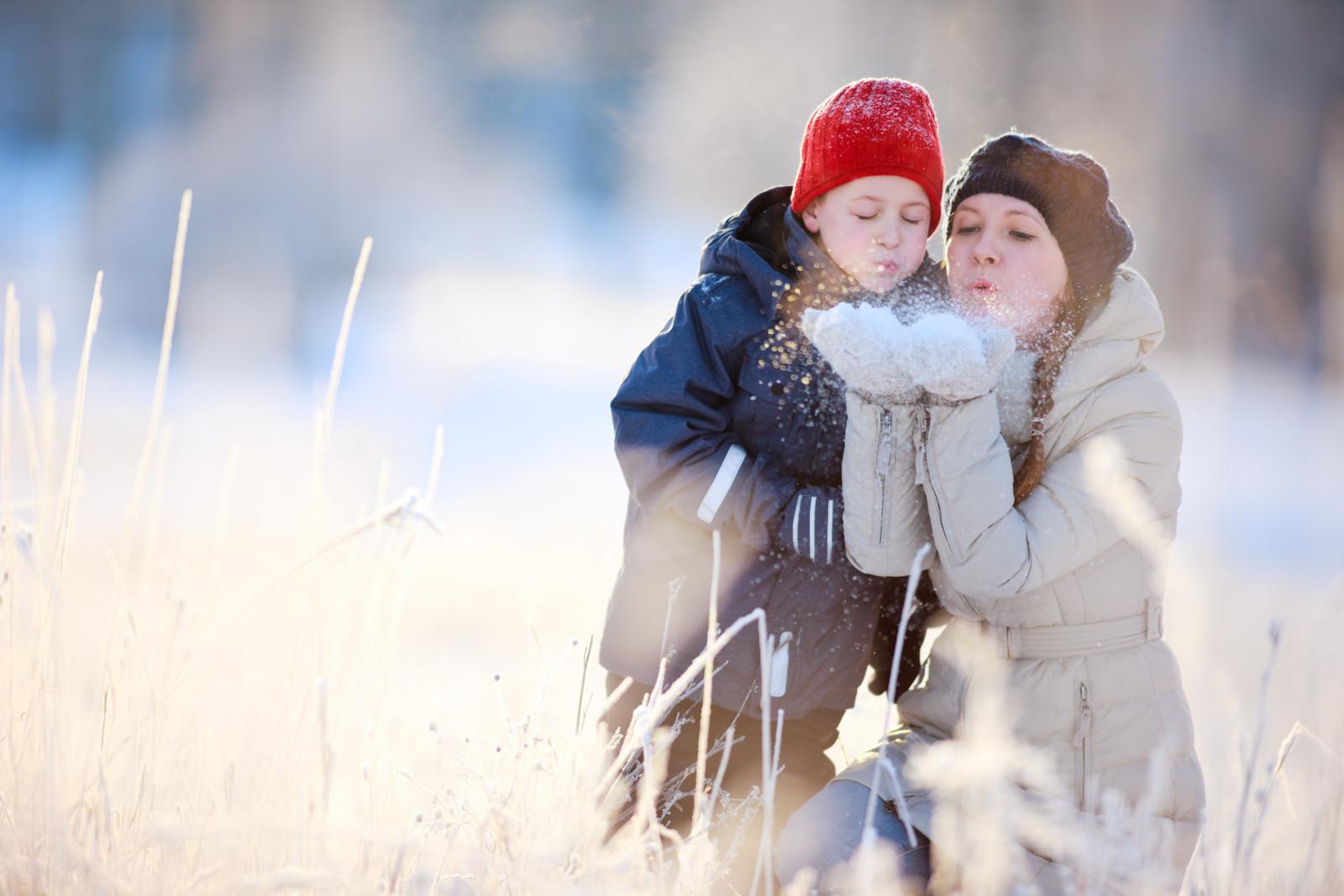 Nainen ja pieni poika puhaltavat lunta naisen käsistä lumisessa maisemassa.