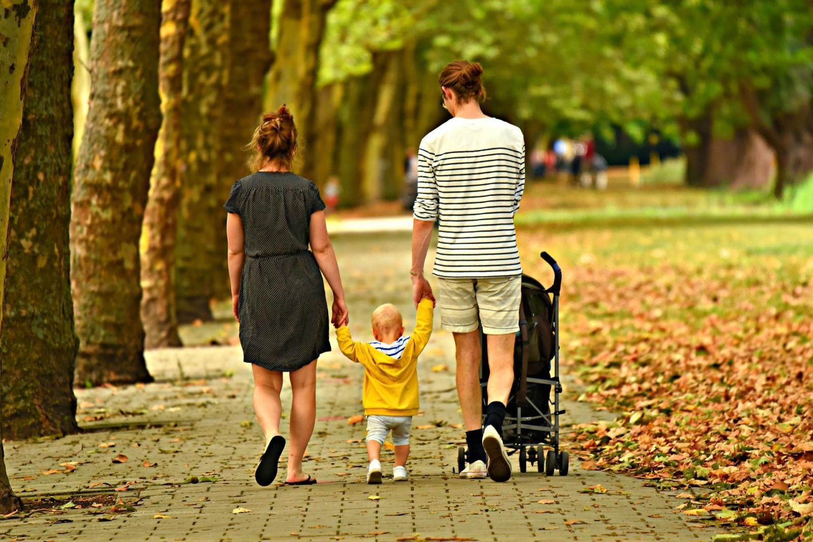 Nainen, mies ja pieni lapsi kävelevät käsi kädessä syksyisessä puistossa. Mies työntää lastenvaunuja.