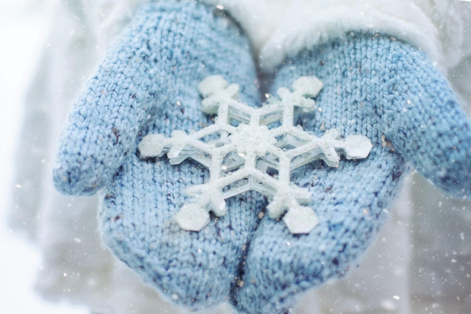 Henkilöllä on kädessään siniset lapaset, joiden päällä on valkoinen lumihiutalekoriste.