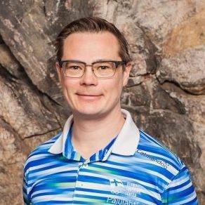 Tummahiuksinen silmälasipäinen mies valko-siniraitaisessa pikeepaidassa.