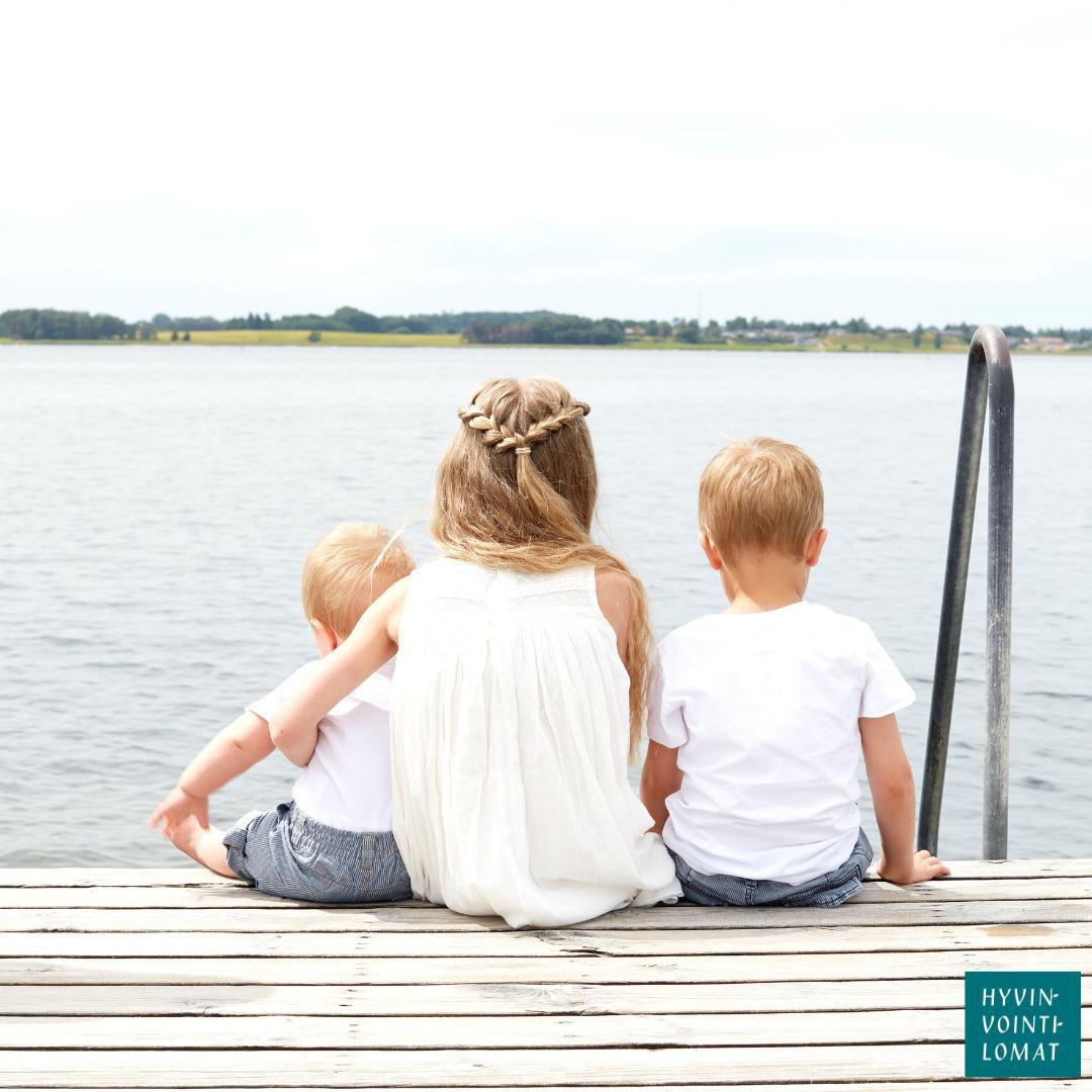 Valkomekkoinen tyttö istuu laiturilla järvi- tai jokimaisemassa. Tyttö pitää vasemmassa kainalossaan valkopaitaista ja harmaahousuista vauvaa. Tytön oikealla puolella istuu valkopaitainen ja farkkuhousuinen lapsi.