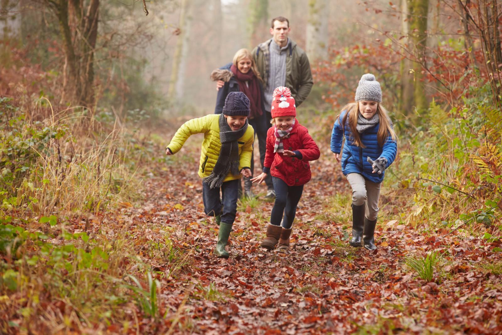 Nainen ja mies kävelevät toisiaan halaten syksyisessä maisemassa. Kuvan etualalla juoksee rinnakkain kolme lasta.